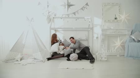 minder : Merry family throws pillows into each other in the New Year s room.