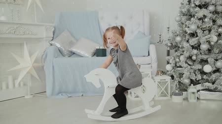 costumes : Very beautiful little girl riding on a wooden horse in the New Years room and smiling.
