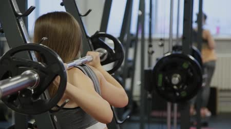 determinado : Very beautiful woman crouches with a barbell on her shoulders.