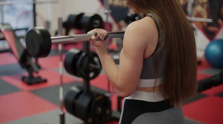 штанга : Very beautiful woman trains biceps with a barbell in the gym.