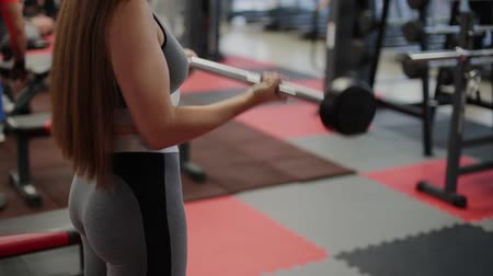 very : Very beautiful woman trains biceps with a barbell in the gym.