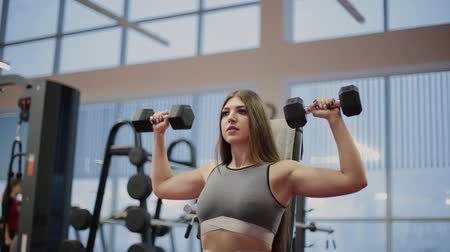 vzpírání : Very beautiful fitness woman exercising with dumbbells in the gym.