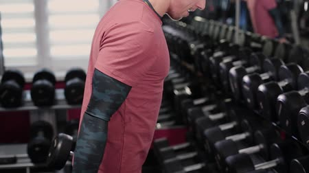 ağır çekimli : Handsome sporty man training dumbbell biceps in the gym.