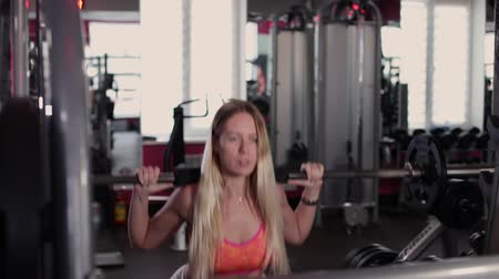 ягодицы : Very beautiful and sexy fitness model trains the legs with an athletic barbell in the gym.