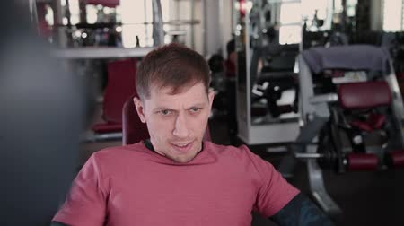 állapot : Athletic and attractive man trains pectoral muscles on a simulator in the gym. Stock mozgókép