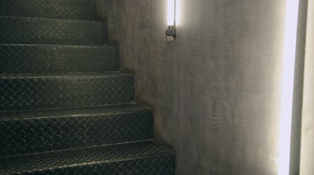 antique grunge : iron metal staircase in the interior with lamps on the wall.