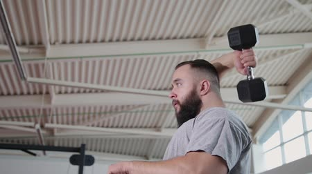 pulling up : Handsome athletic man trains triceps on the block simulator in the gym.