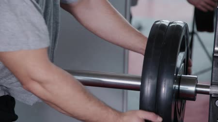 construção muscular : Handsome athletic man puts weight on a barbell in the gym.