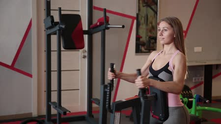 rajstopy : Woman trains arms and shoulders on simulator in gym.