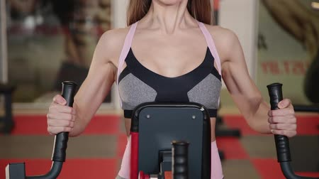 punčocháče : Woman trains arms and shoulders on simulator in gym.
