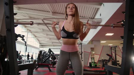 fisiculturismo : Beautiful athletic young girl crouches on the shoulders in the gym. Stock Footage