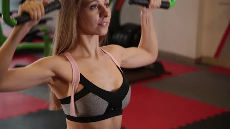 contra : Beautiful athletic young girl performs a pull on the chest simulator in the gym.