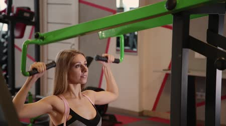 çekme : Beautiful athletic young girl performs a pull on the chest simulator in the gym.