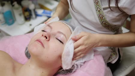 zmarszczki : Very beautiful girl wipes her face with napkins before massaging her face in the spa salon.