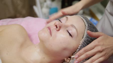 лицевой : Attractive female at spa health club getting a facial massage. Beautician doing massage of face, neck and shoulders of beautyful young woman at luxury beauty salon