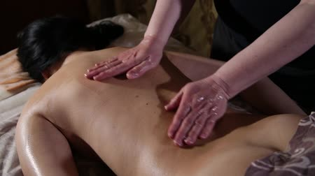 терапия : Very beautiful girl gets a back massage in the spa salon.
