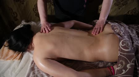 masszőr : Very beautiful girl gets a back massage in the spa salon.