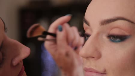 тени для век : Professional makeup artist makes makeup a very beautiful woman. Стоковые видеозаписи