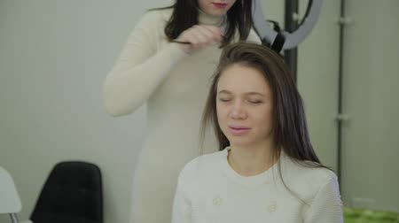 ondulação : Beautiful woman with brown hair is having it treated with a curling iron by a hairdresser. Handheld real time establishing shot.