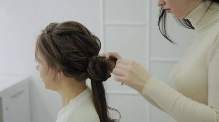 suszarka : A young woman sits in a hairdressers armchair: a hairdresser does a hair styling. A young fair-haired woman came to the beauty salon to make a stylish hairstyle.