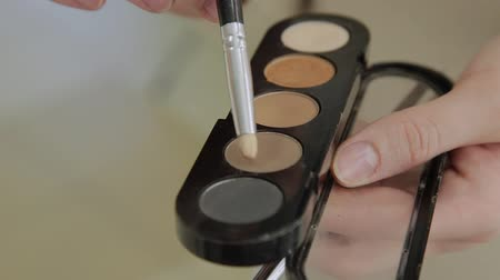 wizaż : A palette with eye shadows and a makeup brush: womens cosmetics. Morning make-up. Decorative cosmetics: a palette with eye shadows, a brush.Evening make-up.Details of the make-up artists work Wideo
