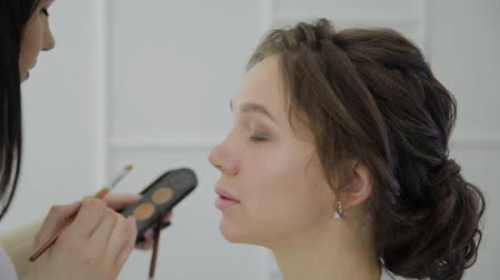 corar : Professional makeup artist makes makeup a very beautiful woman. Stock Footage