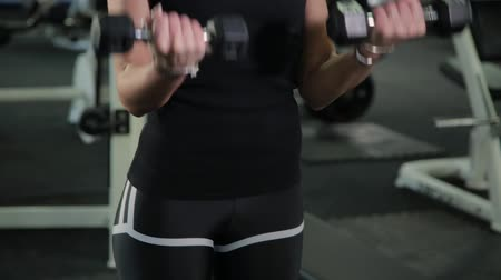 cabeça e ombros : Beautiful athletic young girl trains dumbbells biceps in the gym.