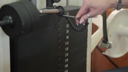 sollevamento pesi : Close-up of a girl changing the bar with the weight on the simulator. Body-building. The girl goes in for sports at the gym, sets the weight on the simulator. Filmati Stock