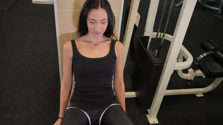 intenzivní : In the gym, a woman spreads her legs on the simulator. Sportswoman sitting on a trainer seat and presses outer surface of the thighs to cushions.