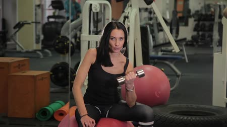 összpontosítás : Young sportive woman sitting on fit ball and lifting dumbbells while training biceps in gym.