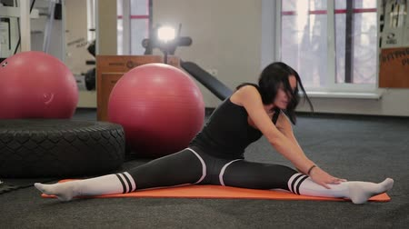 pózy : Young woman exercising at home, stretching legs. Dostupné videozáznamy
