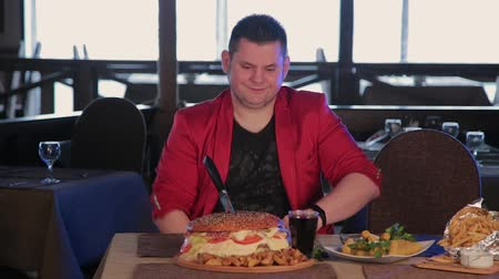 obżarstwo : The man at the table is wearing gloves to eat a burger. Wideo