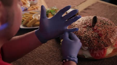 unhealthy eating : The man at the table is wearing gloves to eat a burger. Stock Footage