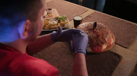 смазка : The man at the table is wearing gloves to eat a burger. Стоковые видеозаписи