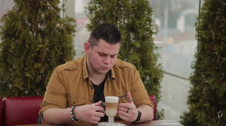 латте : Man drinking latte on the veranda at the table. Стоковые видеозаписи