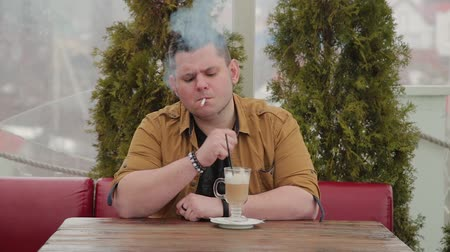 курильщик : Man smoking a cigarette at the table.
