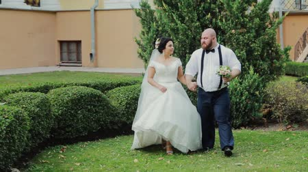 новобрачный : Happy newlyweds walking, hugging, kissing in the park.
