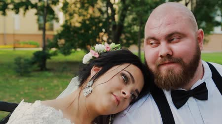 новобрачный : Happy newlyweds are sitting on a bench in the park.