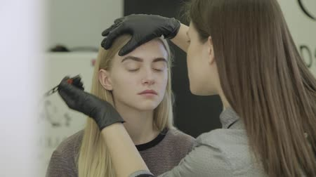 plucks : Makeup artist plucks the eyebrows of a young girl in a beauty salon. Stock Footage
