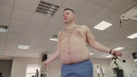 круглолицый : Fat man jumping rope in the gym.
