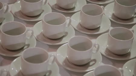 caffe : In the restaurant on a table stand white cups and saucers ranked. Many cups.