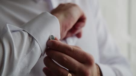 mandzsetta : A successful man fastens cuff links on his shirt, close-up