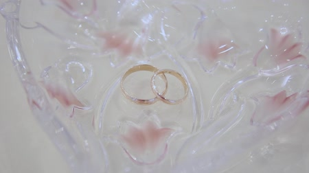 šperk : Beautiful wedding rings on a crystal plate.