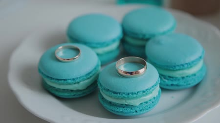 acıbadem kurabiyesi : Fresh and tasty macaroons on a white plate and wedding rings on them.