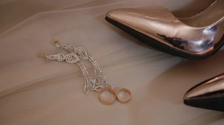 proposta : wedding gold womens shoes rings and jewelry on the bed.