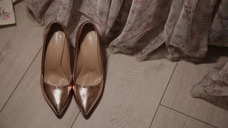 juwelier : gold womens shoes on the floor by the curtain.