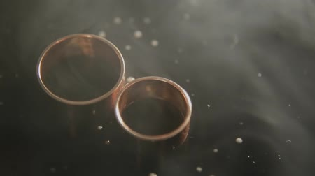 kıymetli : Thick smoke blowing into two wedding RING on wet black background. Close up.