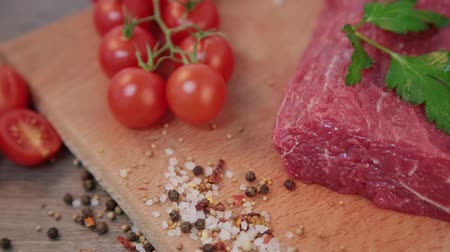 bloody hands : raw beef on a wooden background with spices and tomatoes.