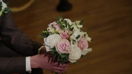 conserva : The man is holding a bouquet with lace ribbons in his hand. Tapes develop in the wind. The groom keeps beautiful flowers. Stock Footage
