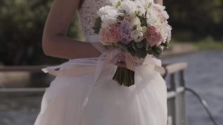 evli : Mid Tilt of a Charming Bride Holding a Delicate Wedding Bouquet. Standing Near the Lake and Looking on the Distance on a Cloudy Day.